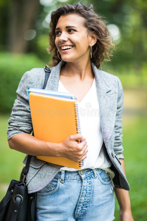 Jolly carefree girl embracing books in park while coming home after classes in university. Cheerful attractive young woman looking. At camera while walking over royalty free stock photo
