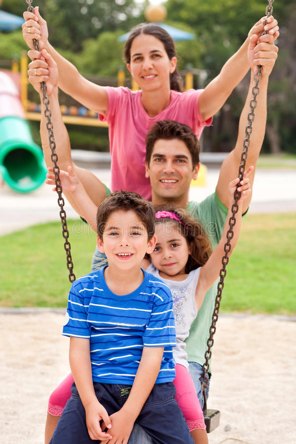 Jolly Caucasian Family Swinging In The Park Stock Photography