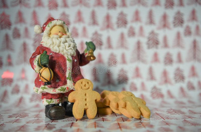 Jolly Christmas-Lebensmittelphotographie-Lebkuchenmann mit Santa Claus-Dekorationsverzierung auf rotem Baumpackpapierhintergrund lizenzfreie stockbilder