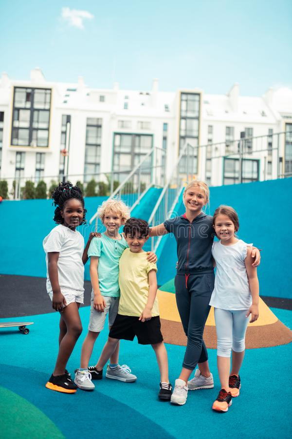 Jolly crowd of children hugging on a sports ground. Friends in a class. Jolly crowd of school children hugging in the middle of a sports ground royalty free stock images