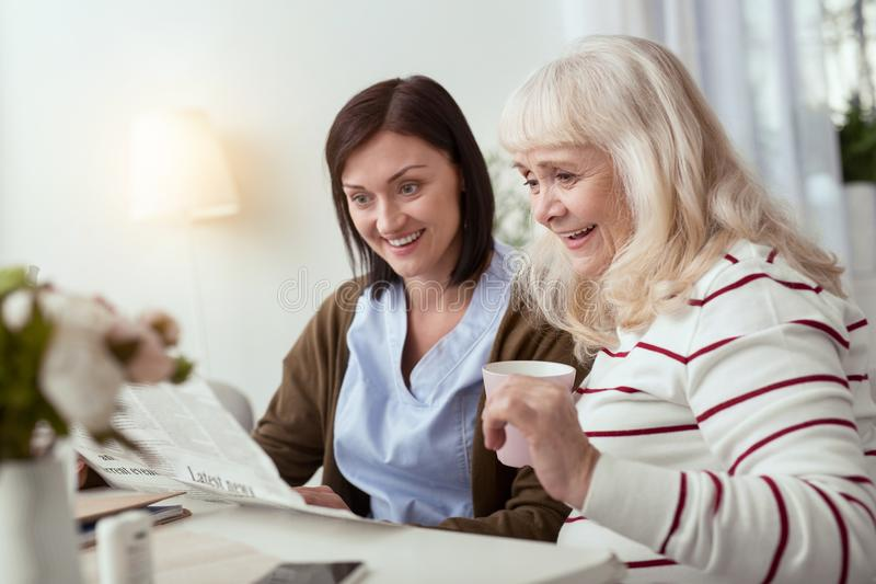 Jolly elder woman and caregiver taking newspaper. Be aware. Joyful elder women and caregiver reading news and communicating stock photography