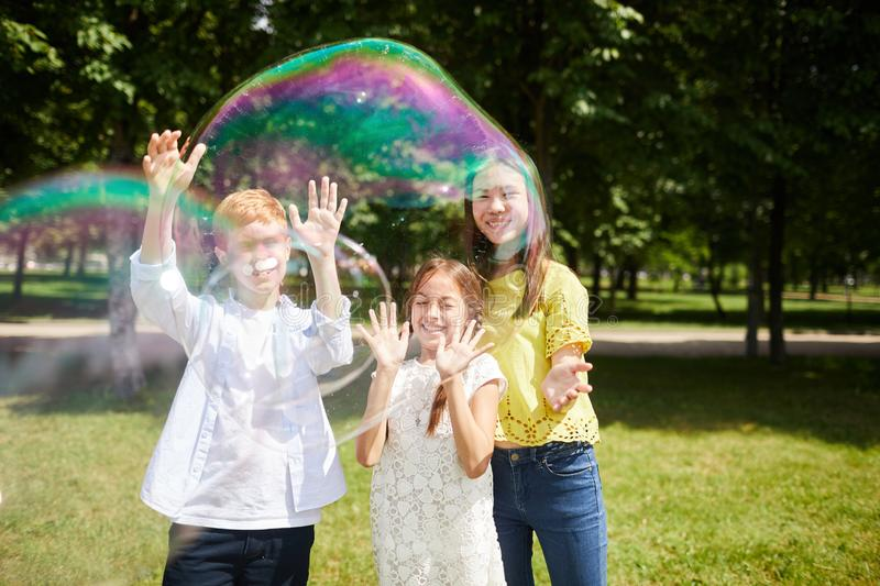 Jolly multi-ethnic kids playing together stock image