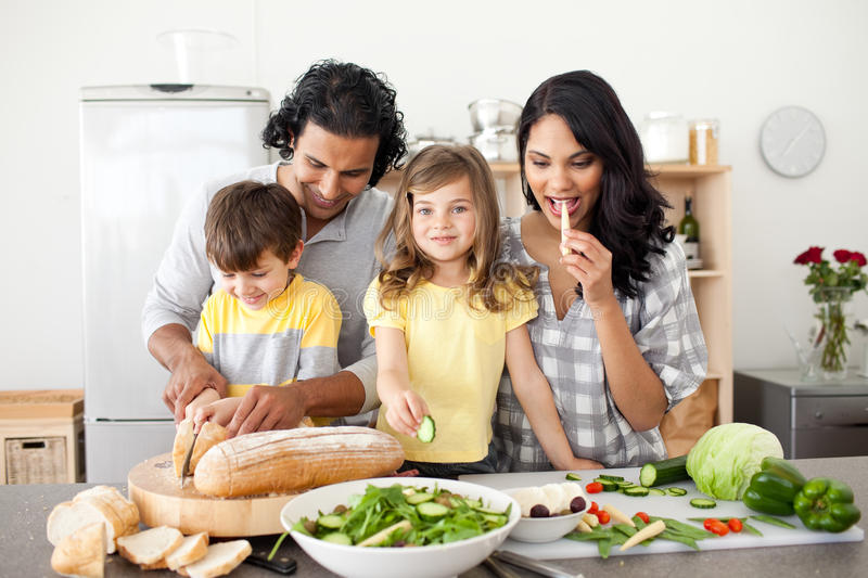 Jolly family preparing lunch together in the kitch stock image