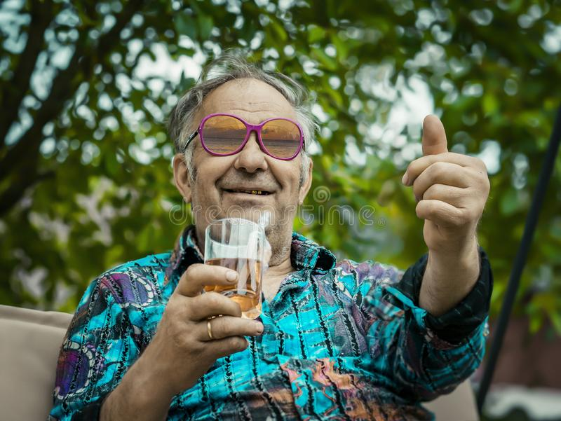 Jolly grandpa shows his thumb up stock photography