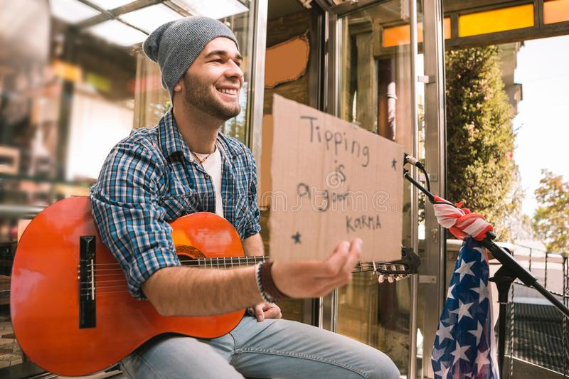 Jolly male musician holding cardboard with inscription stock photo