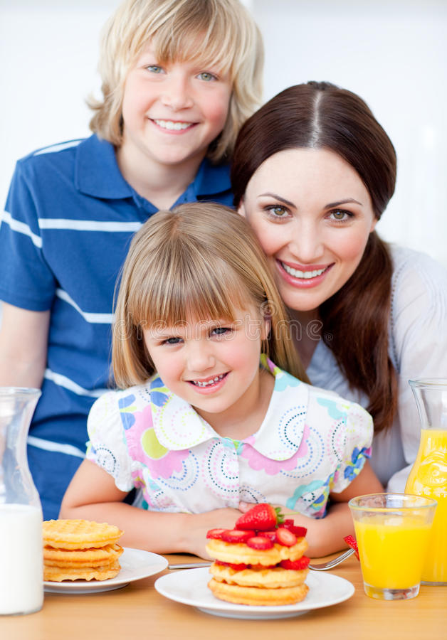 Jolly mother and her children in the kitchen royalty free stock image