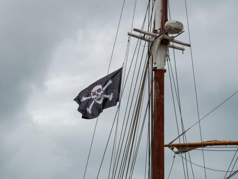 Jolly Roger-/Piratenflagge Totenkopf mit gekreuzter Knochen-Fliegen vom Mast eines Segelschiffs stockfotos