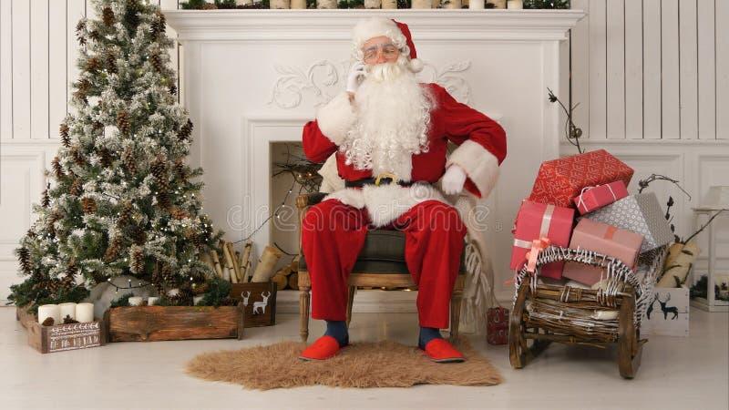 Jolly Santa Claus, der durch den Weihnachtsbaum sitzt und am Telefon spricht stockfotografie