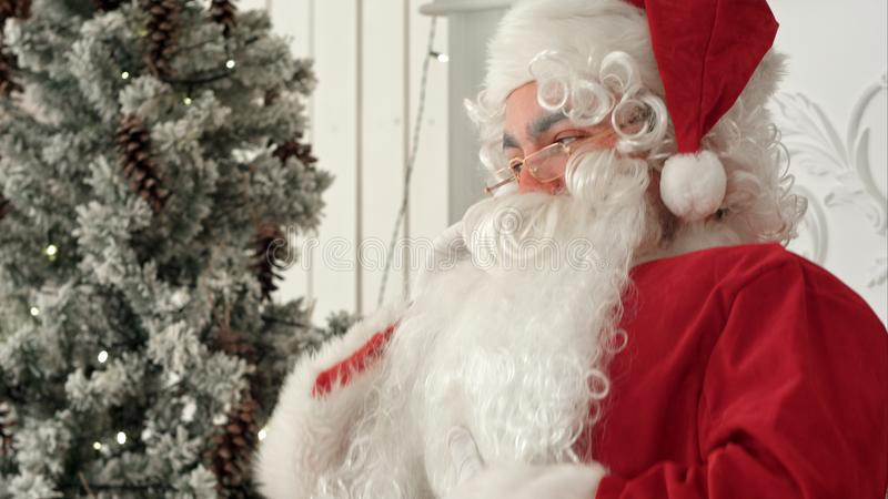 Jolly Santa Claus sitting by the Christmas tree and talking on the phone stock photos