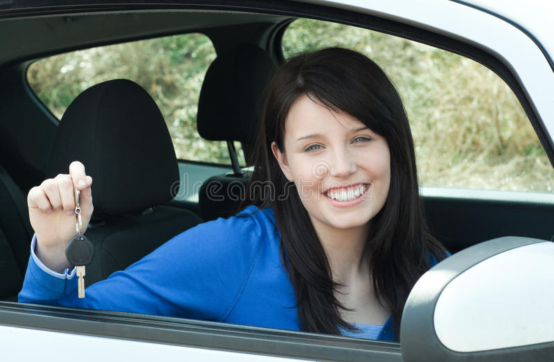 Jolly teen girl sitting in her car holding keys stock photo