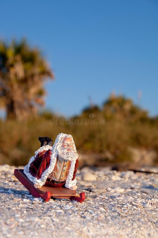 Tropical Santa on a sleigh at the beach. Jolly tropical Santa on a sleigh at the beach on sand and shells at Christmas royalty free stock photography
