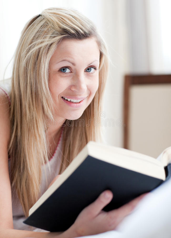 Jolly Woman Reading A Book Lying On Her Bed Stock Images