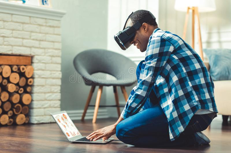 Jolly young afro american man choosing software. First step. Vigorous afro american man putting on VR glasses and sitting on floor royalty free stock photography