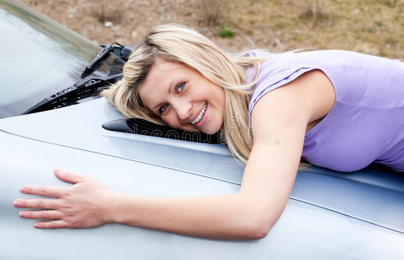 Jolly young driver hugging her new car. Jolly young female driver hugging her new car royalty free stock images