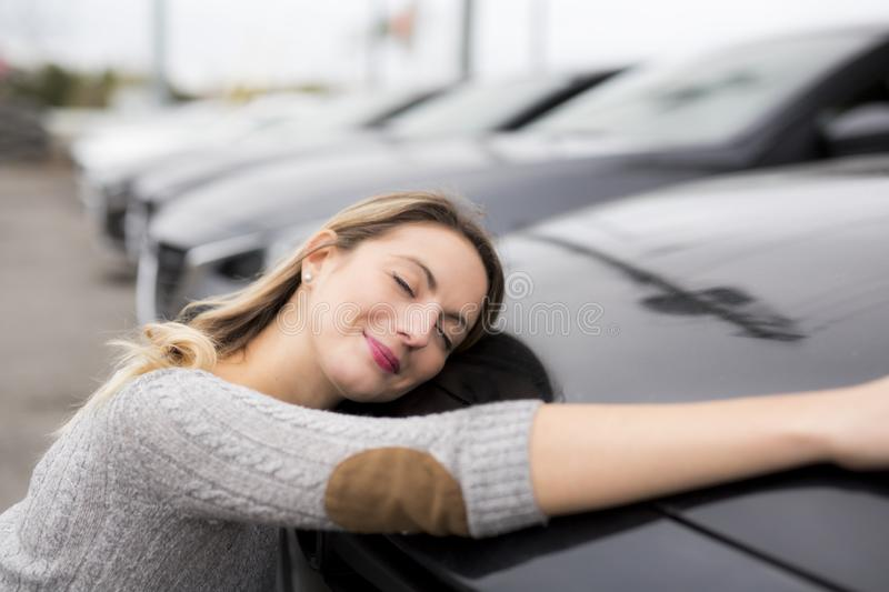 Jolly young female driver hugging her new car. A Jolly young female driver hugging her new car stock photography