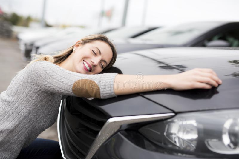 Jolly young female driver hugging her new car. A Jolly young female driver hugging her new car royalty free stock photography