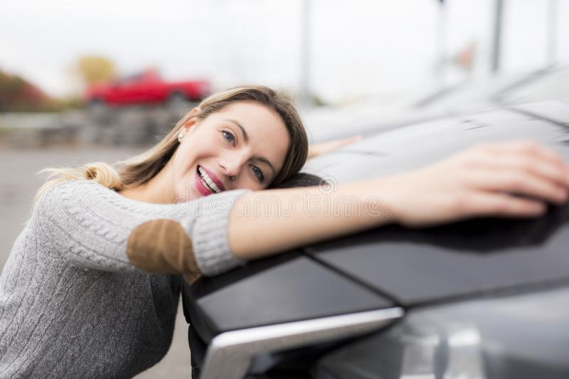 Jolly young female driver hugging her new car. A Jolly young female driver hugging her new car stock image