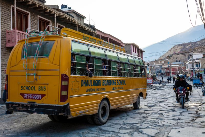 Jomsom,尼泊尔- 2015年11月19日:乘坐学校班车的孩子对学校在清早在Jomsom,野马,尼泊尔 图库摄影