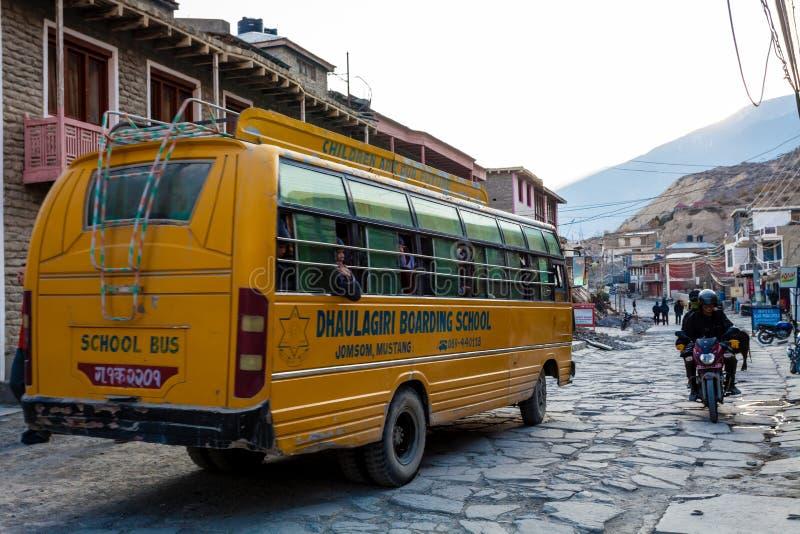 Jomsom, Nepal - 19 de novembro de 2015: Crianças que montam um ônibus escolar à escola no amanhecer em Jomsom, mustang, Nepal fotografia de stock