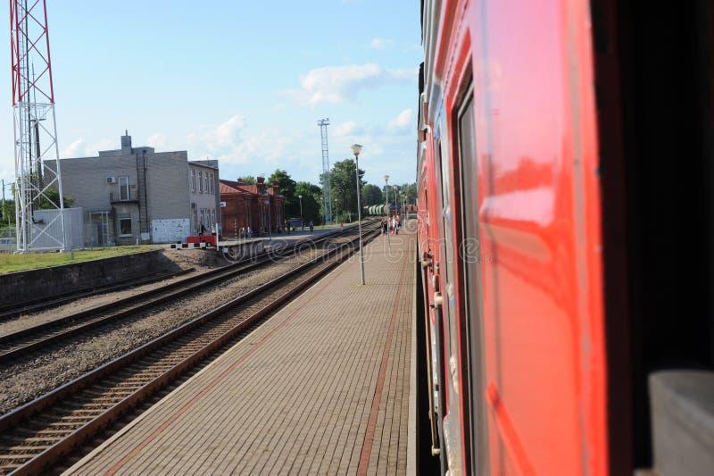JONAVA, ЛИТВА - 26-ОЕ ИЮНЯ 2011: Сеть и след Литвы железнодорожная Идти на скорый поезд Причаливать к станции стоковые фотографии rf