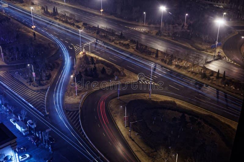 Jonction lumineuse d'autoroute par nuit avec des traces de lumière bleue et rouge photos stock
