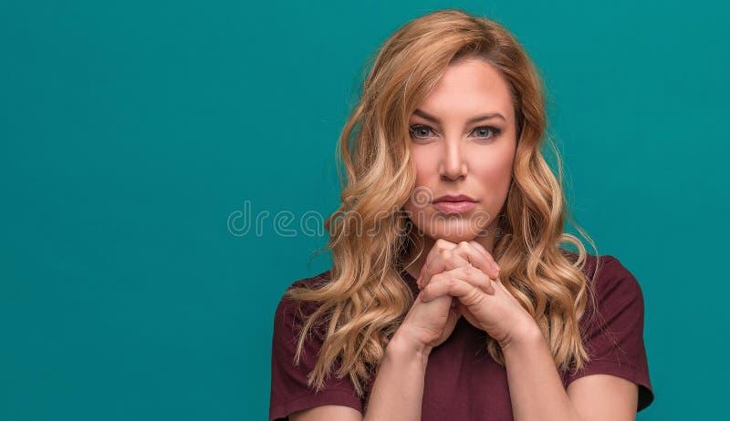 Jong aantrekkelijk blonde op een blauwe achtergrond royalty-vrije stock afbeelding