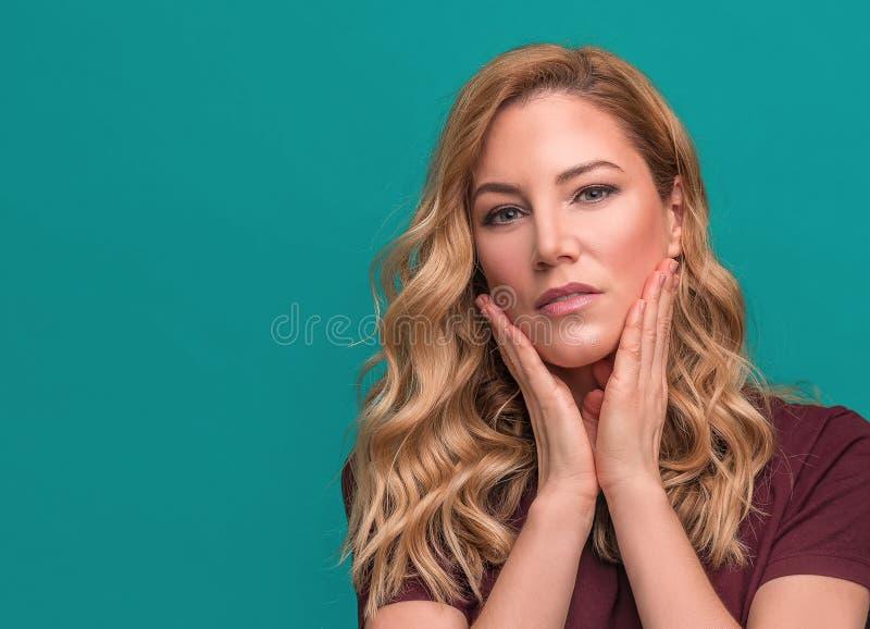 Jong aantrekkelijk blonde op een blauwe achtergrond stock afbeeldingen