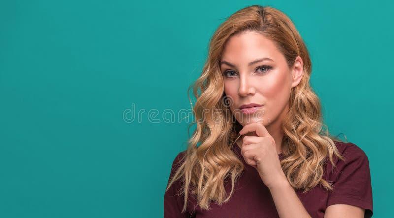 Jong aantrekkelijk blonde op een blauwe achtergrond stock fotografie
