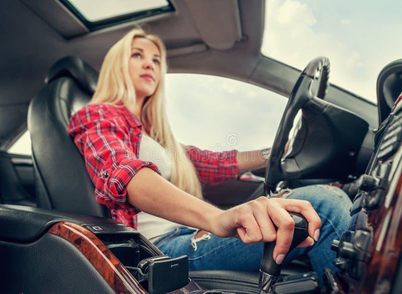 Jong aantrekkelijk blondemeisje die een auto met een automatische versnellingsbak drijven stock foto's