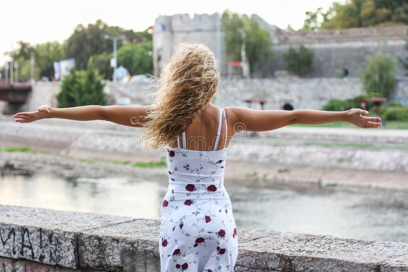 Jong Aantrekkelijk Blondemeisje die Haar Wapens uitspreiden royalty-vrije stock fotografie