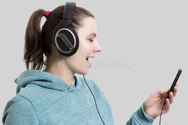 Jong aantrekkelijk donkerbruin meisje in hoofdtelefoons met speler Beauti stock foto
