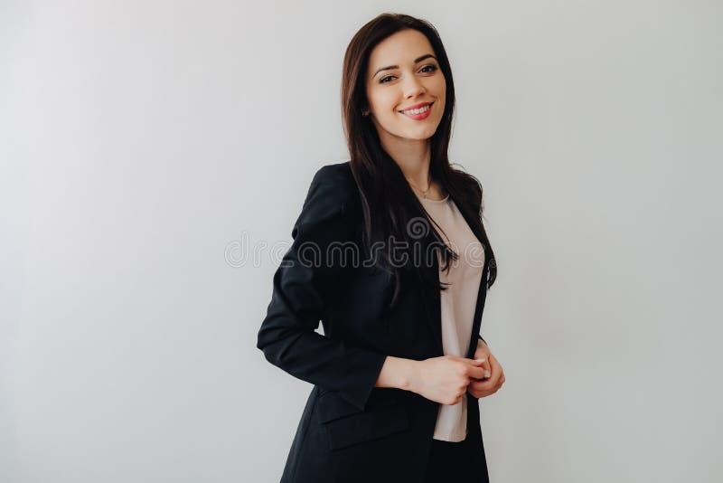 Jong aantrekkelijk emotioneel meisje in zaken-stijl kleren op een duidelijke witte achtergrond in een bureau of een publiek stock foto's