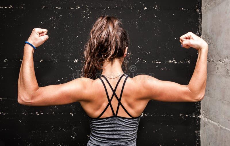 Jong aantrekkelijk geschiktheidsmeisje die haar achterspieren na harde training in de gymnastiek tonen stock foto's