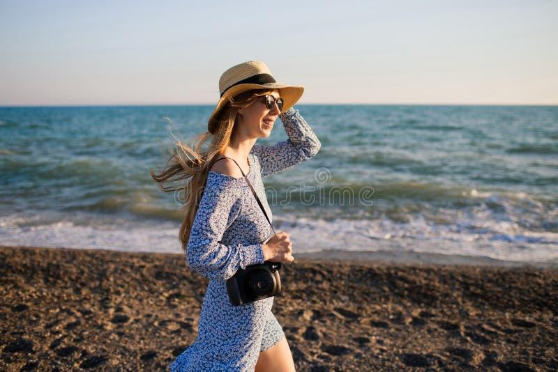 Jong aantrekkelijk glimlachend meisje die langs het strand lopen stock foto's