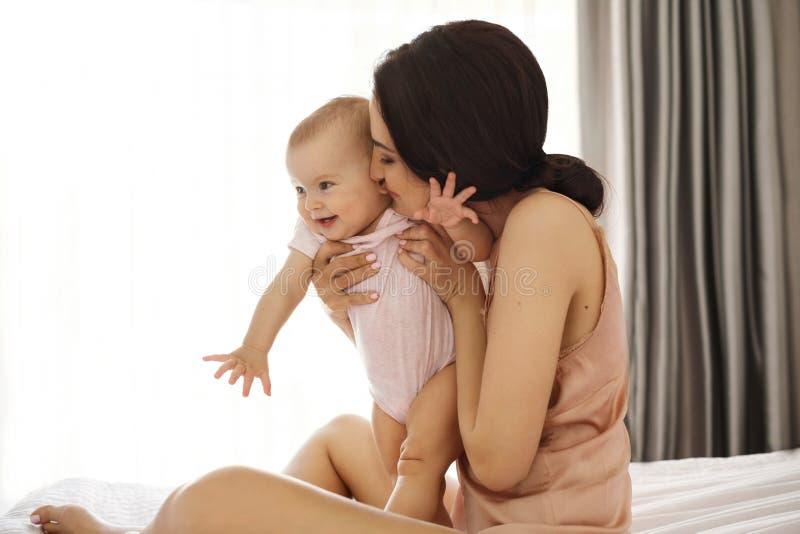 Jong aantrekkelijk mamma in nachtkleding het glimlachen het koesteren kussend haar babyzitting in bed over venster Gesloten Ogen stock foto's