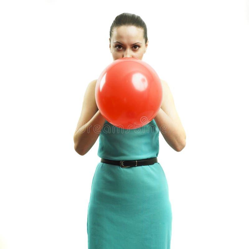 Jong aantrekkelijk meisje dat een ballon opblaast stock fotografie