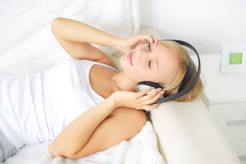 Jong aantrekkelijk meisje die aan muziek in hoofdtelefoons luisteren royalty-vrije stock foto