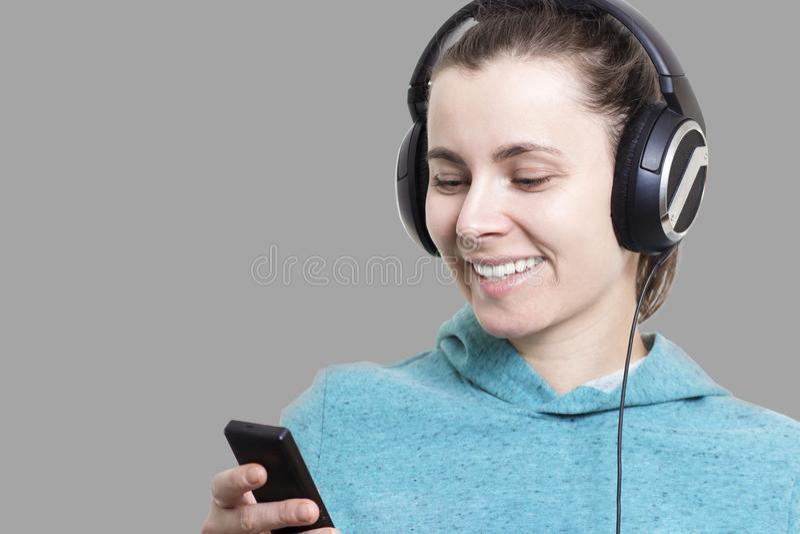 Jong aantrekkelijk meisje met speler en in hoofdtelefoons die die aan popmuziek luisteren op grijze achtergrond wordt geïsoleerd  royalty-vrije stock fotografie