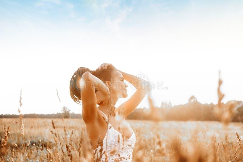 Jong aantrekkelijk meisje op gebied bij zonsondergang stock foto