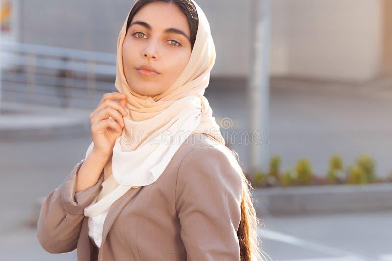 Jong aantrekkelijk meisje in pak en hijab in straat stock afbeelding