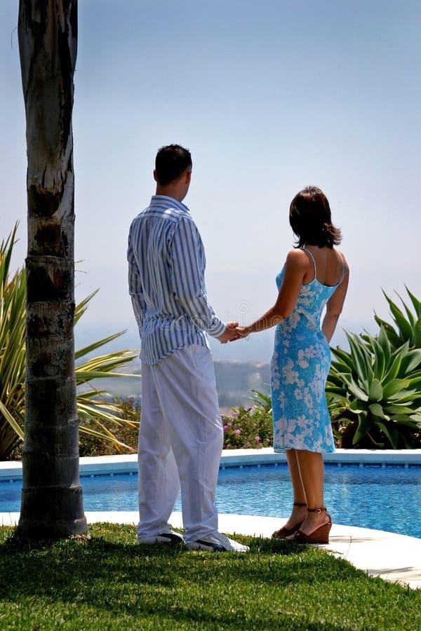 Jong aantrekkelijk paar in de handen van de liefdeholding onder een palm stock afbeelding