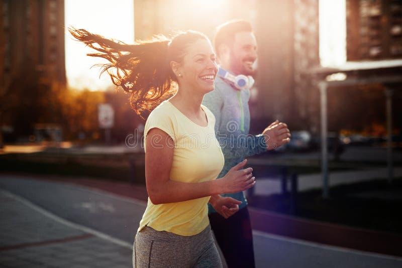 Jong aantrekkelijk paar die buiten op zonnige dag lopen stock foto's
