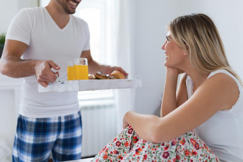 Jong aantrekkelijk paar die ontbijt in bed hebben stock afbeeldingen