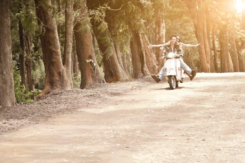 Jong aantrekkelijk paar die op autoped langs landweg reizen stock foto's