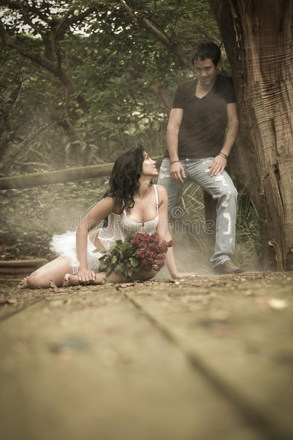 Jong aantrekkelijk paar die op houten dek in bos flirten stock afbeelding