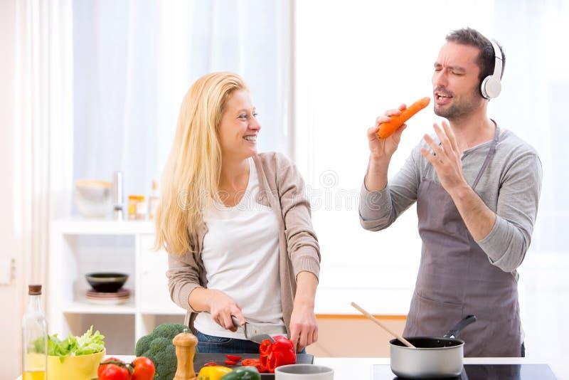 Jong aantrekkelijk paar die pret in de keuken hebben royalty-vrije stock foto's