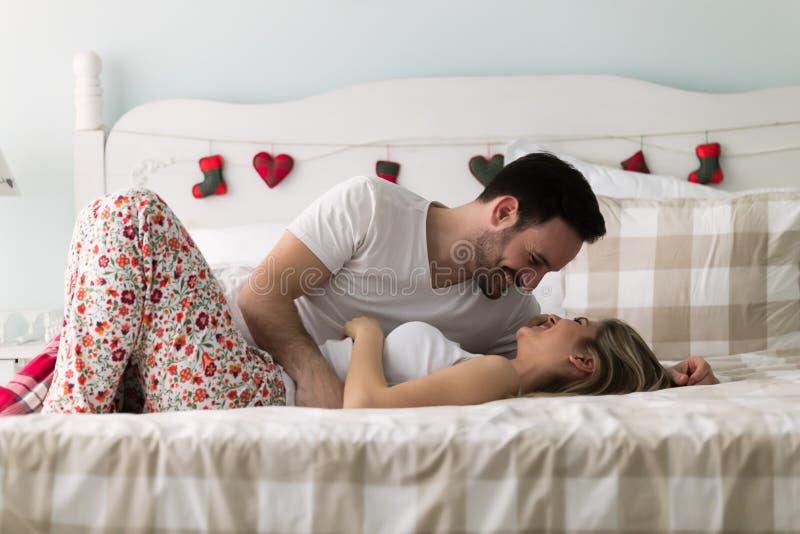 Jong aantrekkelijk paar die romantische tijd in bed hebben stock afbeelding