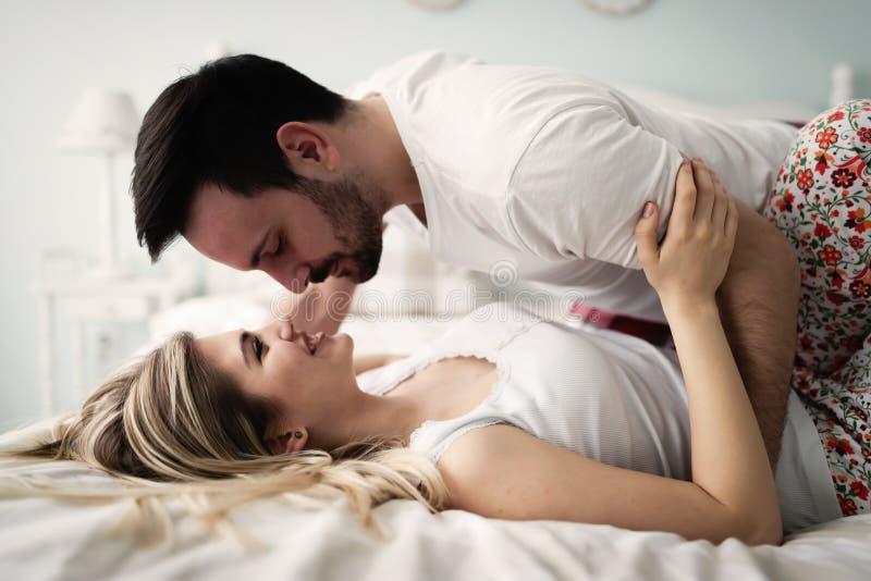Jong aantrekkelijk paar die romantische tijd in bed hebben stock afbeeldingen