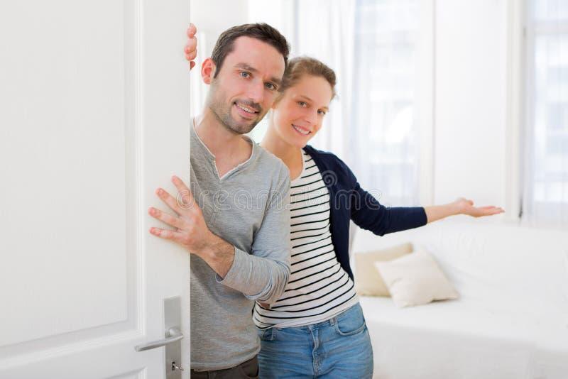 Jong aantrekkelijk paar die u welkom heten in zijn huis stock fotografie