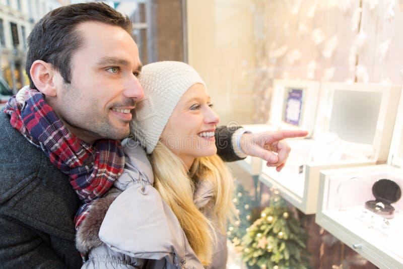 Jong aantrekkelijk paar die wat venster het winkelen doen stock fotografie